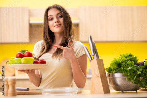 Young woman preparing salad at home in kitchen - 221645114