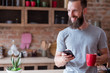 modern lifestyle and mobile devices addiction. smiling man standing in the kitchen having a cup of tea or coffee and using his phone.