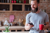modern lifestyle and mobile devices addiction. smiling man standing in the kitchen having a cup of tea or coffee and using his phone. - 221647595