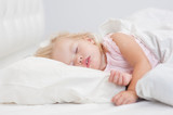 little baby girl sleeping on a bed - 221652309