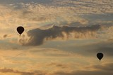 Balloons fly in the evening against the backdrop of the setting sun with clouds