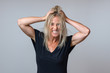 Frustrated woman tearing at her long blond hair
