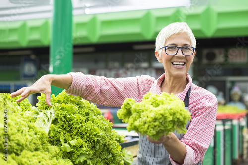 Senior woman sells lettuce on marketplace - 221668542