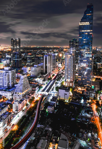Foto Murales Night architecture. Skyscrapers with glass facade. Modern buildings in Bangkok business district. Evening dynamic traffic on a street. Business, economy and finances concept.