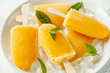 Leinwanddruck Bild - Popsicles, ice lollies on stick with sweet orange juice in white plate with ice
