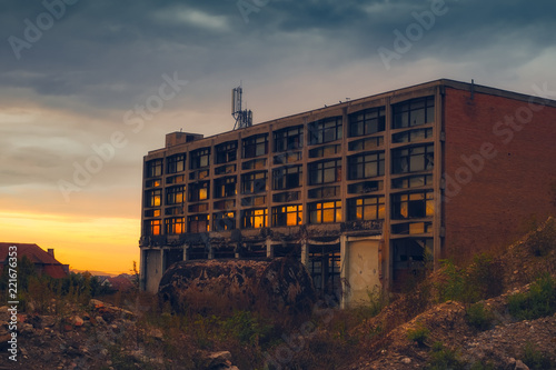 Leinwanddruck Bild sunset reflected in the broken windows of the abandoned industrial building