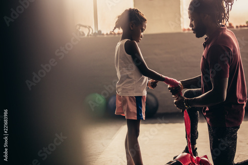 Coach wrapping a bandage on the hands of a kid boxer - 221683986