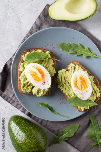 Avocado toasts with eggs and salad on breakfast - 221690590