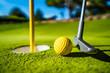 Leinwandbild Motiv Mini Golf yellow ball with a bat near the hole at sunset