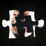 Hand inserting the missing piece of the puzzle - view from the bottom - 221691545