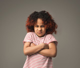 Cute little angry black girl at gray background - 221692323