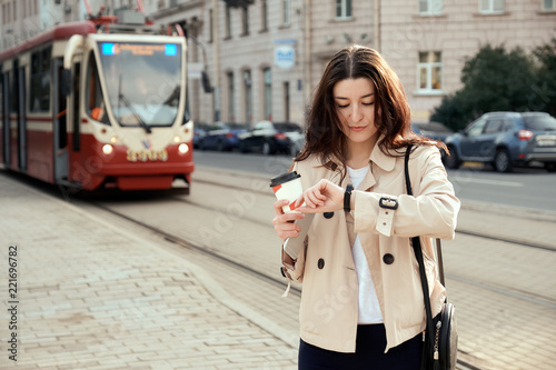 Pretty young woman waiting for train or tram as arrival, checking the time on smartwatch, drinking takeout coffee cup. Train rides in the background. Urban lifestyle concept.