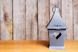 Metal home-shaped lantern with heart-shaped hole on a wooden background - 221697131