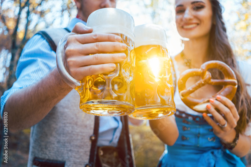 Leinwanddruck Bild Frau und Mann in Bayerischer Tracht trinken Bier