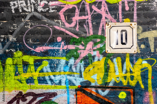 A wall with graffiti of unknown artists. Number of the house on the wall. Street art. Copyspace for text and design - 221698764
