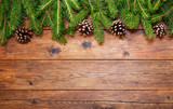 Christmas wooden background with fir branches and cones, top view - 221701197