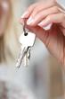 Leinwanddruck Bild - Frau hält Schlüssel in ihren Fingern