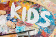 Leinwanddruck Bild - Words kids painted with white gouache on palette of artist with mixture of colors
