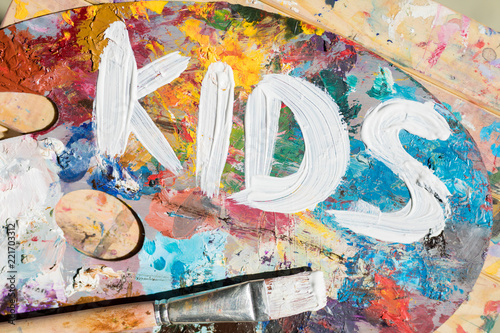 Leinwanddruck Bild Words kids painted with white gouache on palette of artist with mixture of colors