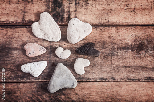 Heart shaped stones in a circle on a wooden background - 221705139