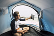 Travel and use technology to communicate for young handsome teenager sitting in side a tent camped on the beach and using a teblaet internet cnnected to send messages and video conference with parents