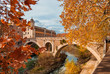 Leinwanddruck Bild - Autumn and foliage in Rome. Red and yellow leaves near Tiber Island with ancient roman bridge, in the city historic center