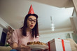 A girl in a cap alone with a cake with candles sitting on the sofa in the room.