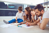 A family draws on paper lying on their free time on the floor in the room. - 221712725