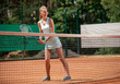 Leinwanddruck Bild - Smiling young female is standing on court in front of net. She is bending and holding racket with both hands while getting ready to hit. Copy space in right side