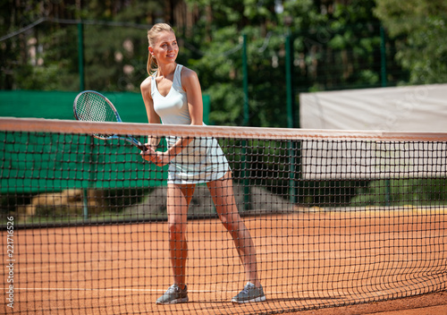 Leinwanddruck Bild Smiling young female is standing on court in front of net. She is bending and holding racket with both hands while getting ready to hit. Copy space in right side