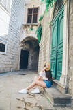 woman sitting on stairs outside at summer day - 221717907
