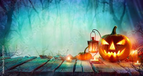 Leinwandbild Motiv Halloween - Jack O' Lanterns And Candles On Table In Misty Night