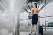 Full length portrait of business lady is standing with suitcase and holding cellphone at the airport. Copy space in left side
