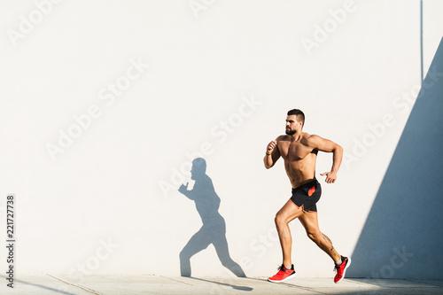 Fototapeta Athletic build man running outdoors