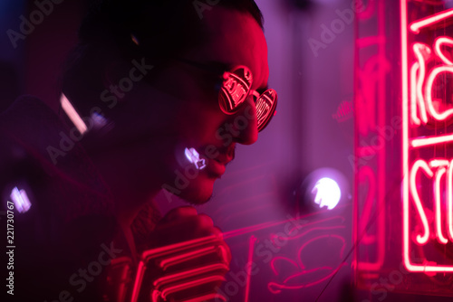 Naklejka man with stubble and sunglasses looking at neon sign