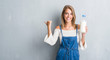 Leinwanddruck Bild - Beautiful young woman over grunge grey wall holding bottle of fresh milk pointing and showing with thumb up to the side with happy face smiling