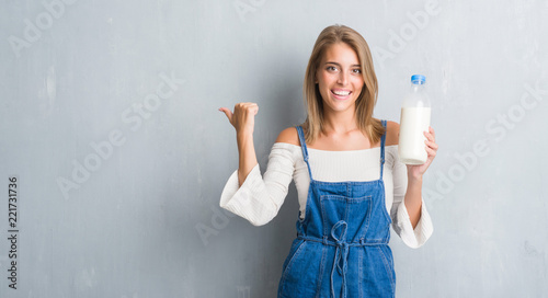 Leinwanddruck Bild Beautiful young woman over grunge grey wall holding bottle of fresh milk pointing and showing with thumb up to the side with happy face smiling