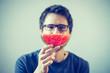 Junger Mann hält sich ein Stück Melone vor das Gesicht, Konzept
