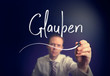 """A businessman writing a Believe """"Glauben"""" concept in German with a white pen on a clear screen."""