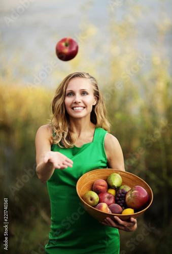 Kobieta w zielonej sukience trzymająca miskę z owocami