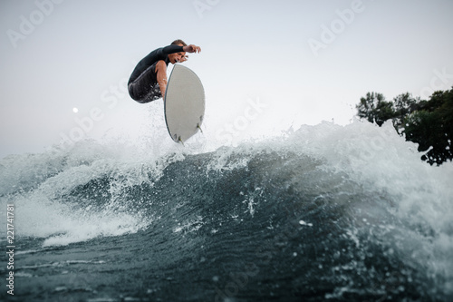 Young and active wakeboarder jumping on the blue splashing wave against the background of clear sky on the foreground