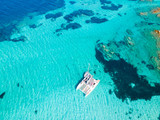 Drone aerial view of catamaran sailing boat in Maddalena Archipelago, Sardinia, Italy. Maddalena Archipelago is a group of islands between Corsica and north-eastern Sardinia. - 221746917