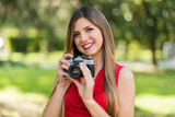 Smiling young woman holding a camera - 221759786