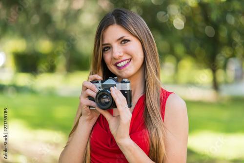 Leinwanddruck Bild Smiling young woman holding a camera