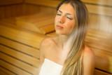 Beautiful woman having a sauna bath in a steam room - 221760137
