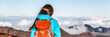 Travel hiker wanderlust adventure woman on trek hike above mountain clouds banner panorama.