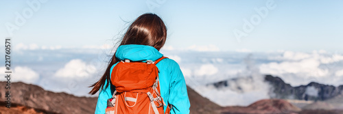 Leinwanddruck Bild Travel hiker wanderlust adventure woman on trek hike above mountain clouds banner panorama.