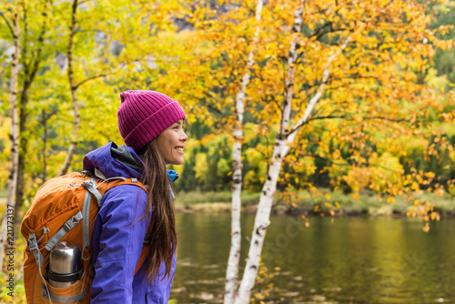 Leinwanddruck Bild Woman hiker hiking looking at scenic view of fall foliage mountain landscape . Adventure travel outdoors person standing relaxing near river during nature hike in autumn season.