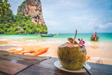 Coconut fruit drink at beautiful Tropical Beach blue ocean background with Traveler items  vacation travel accessories for holiday or long weekend a guide  choice idea for planning travel - 221774327