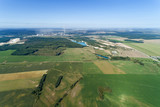 European plain landscape, view from a great height. In the distance are visible factories with smoking pipes - 221780301